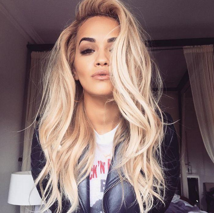 coloration blond platine de rita ora cheveux long ondulés avec volume veste de cuir tee shirt blanc