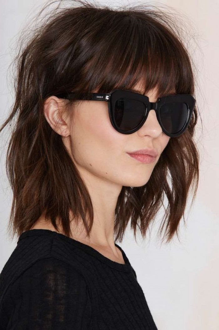 coupe carré avec frange brune aux lunettes de soleil noires rondes femme au top noir