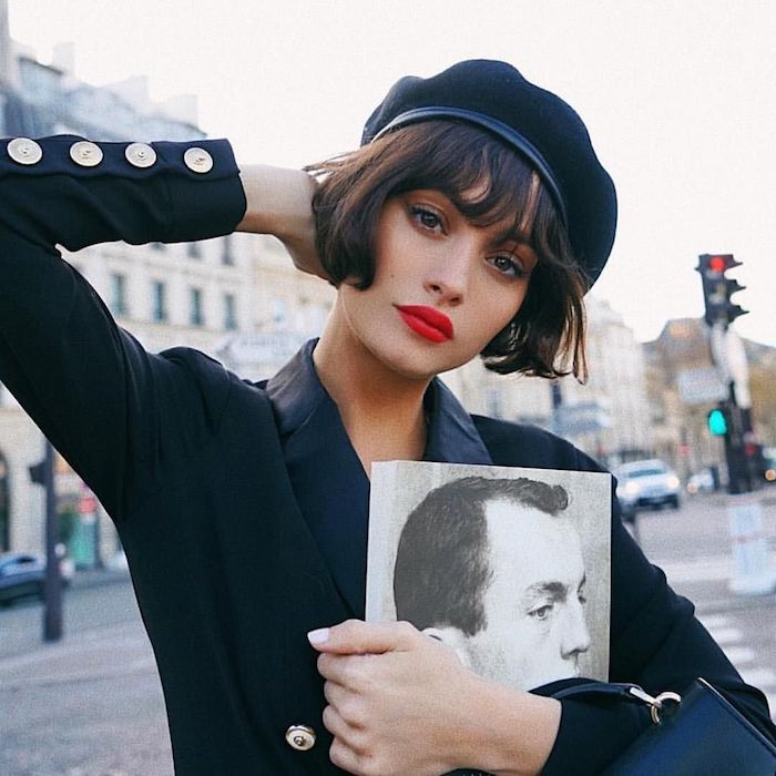 coupe carré avec frange droite légèrement ondulée femme à la tenue noire chapeau noir et lèvres rouges