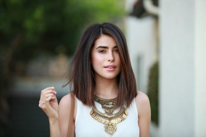 coupe cheveux longs chatain foncé avec mèches sourcils arqués top blanc accessoires en or
