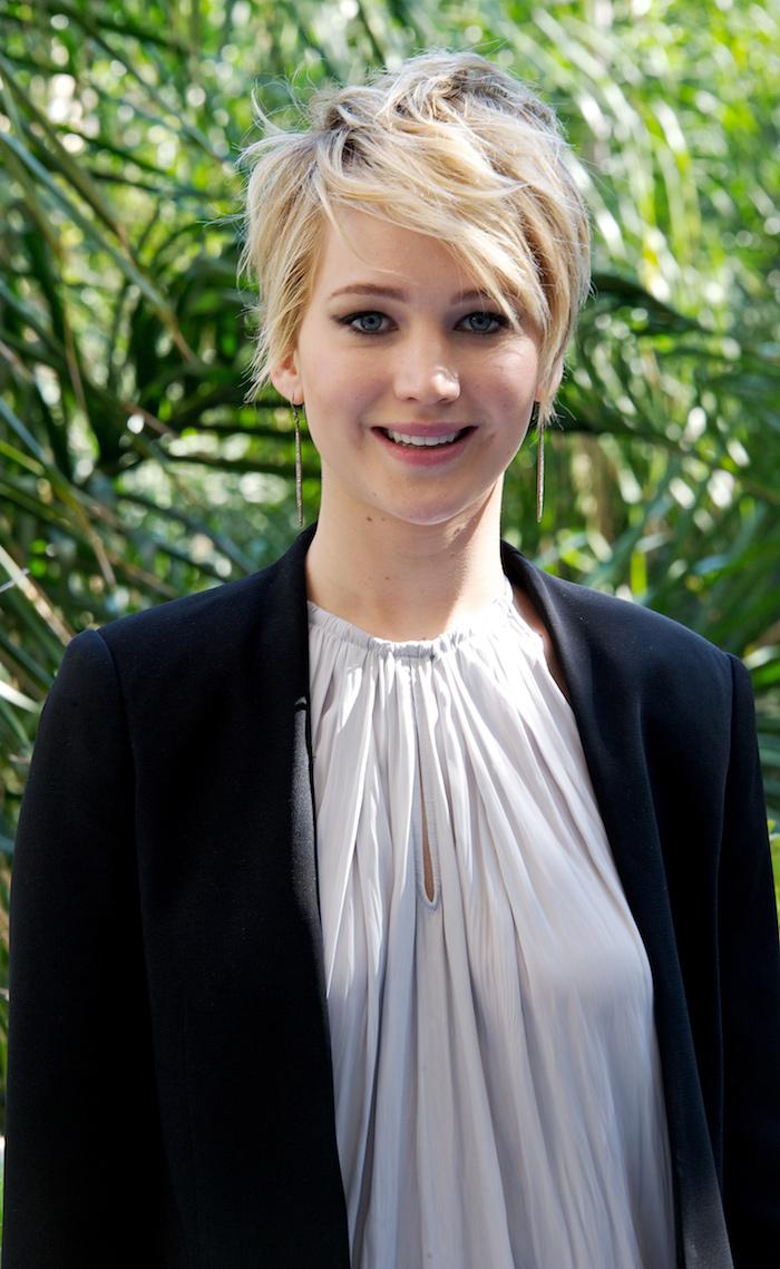 coupe courte asymétrique blonde avec frange effilée sur le cote jennifer lawrence en top gris et veste noire