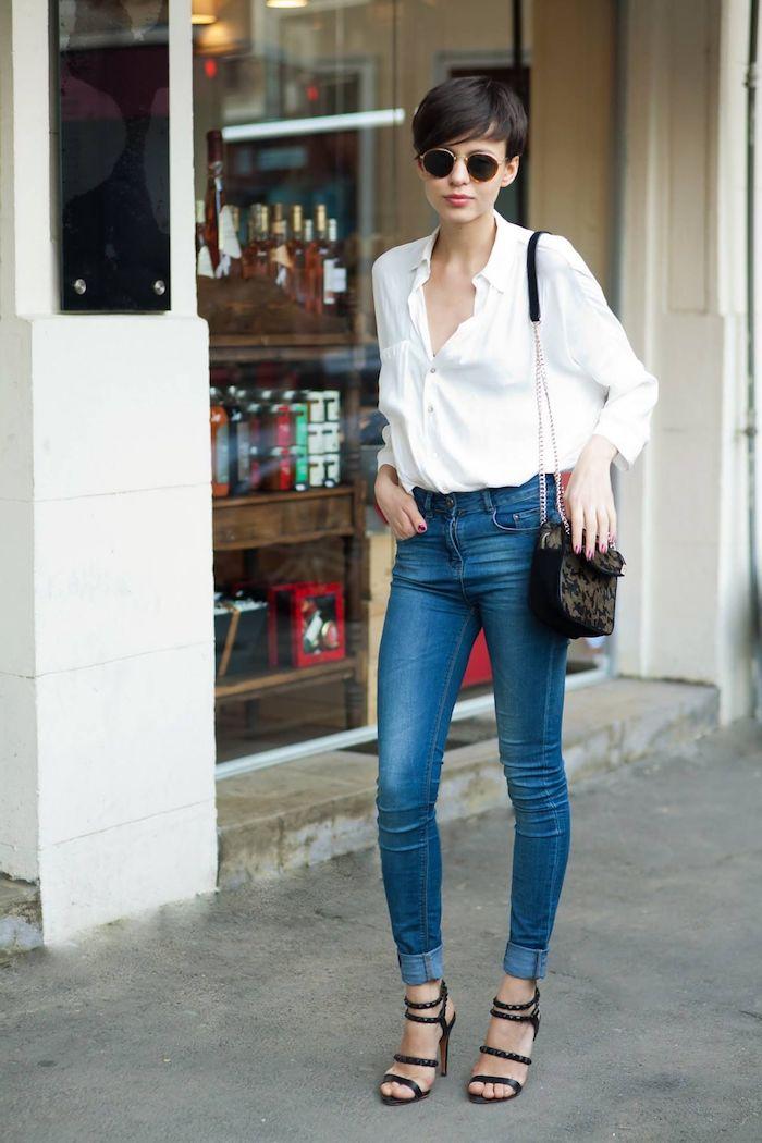 coupe courte asymétrique peinte en cacao avec frange femme aux lunettes de soleil sac à main sandales à talons noirs chemisier blanc et jeans bleus