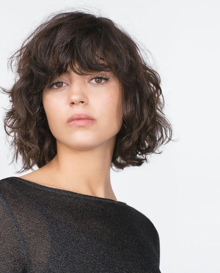coupe courte avec frange brune et ondulée femme à la tenue noire légèrement transparente