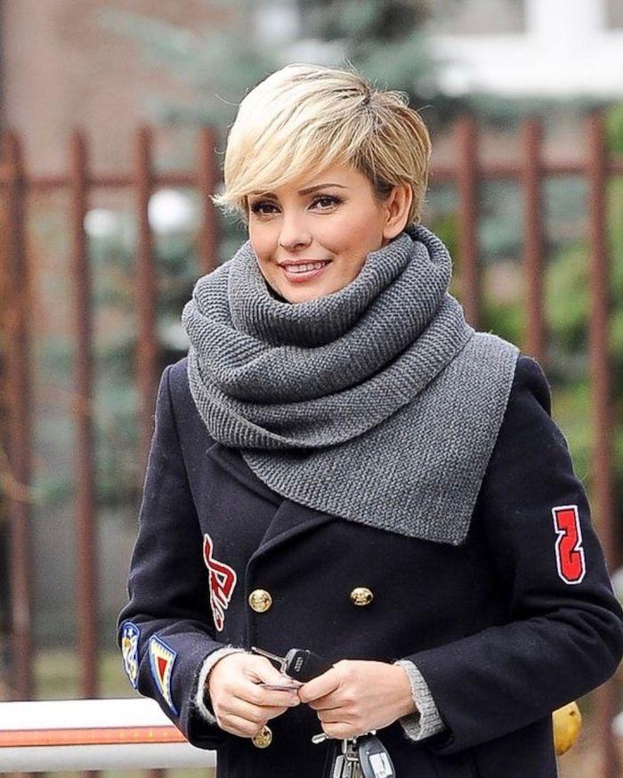 coupe courte blonde avec frange effilée blonde à l écharpe grise et au manteau noir