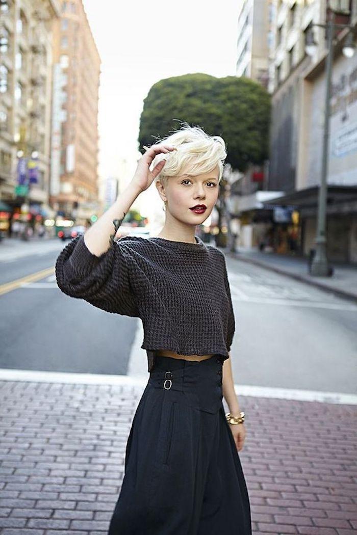 coupe courte blonde dégradée avec frange effilée femme blonde au pull over gris foncé et à la jupe longue noire