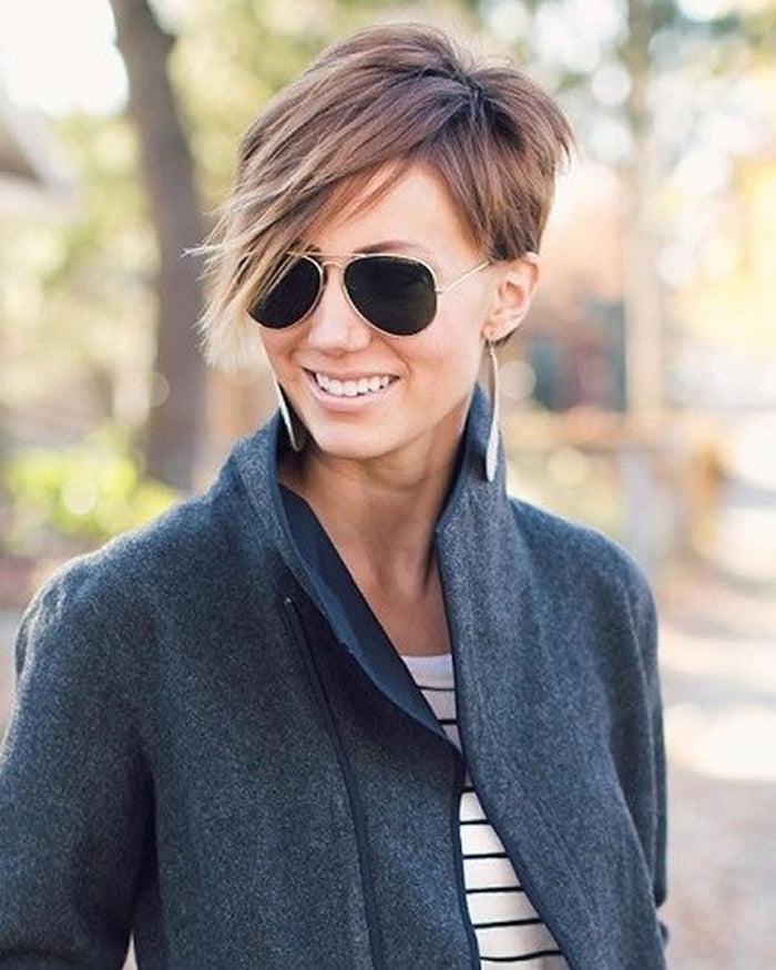 coupe dégradée courte avec frange dégradée femme aux lunettes de soleil noires au manteau gris foncé