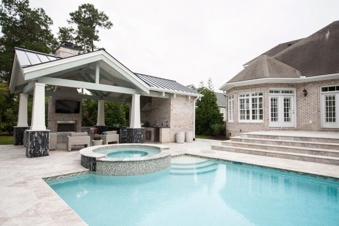 cuisine d été avec piscine aménagement en u façade pierre meuble de jardin tressé beige