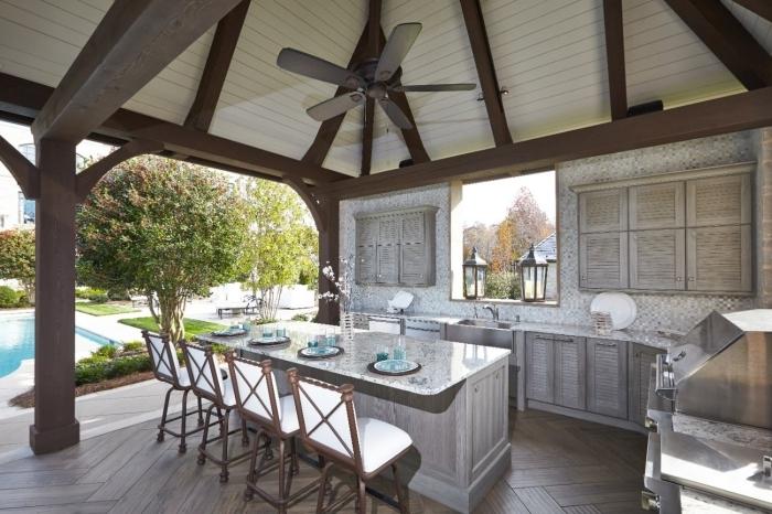 cuisine extérieure couverte ventilateur de plafond poutres bois style vintage rustique armoires grises