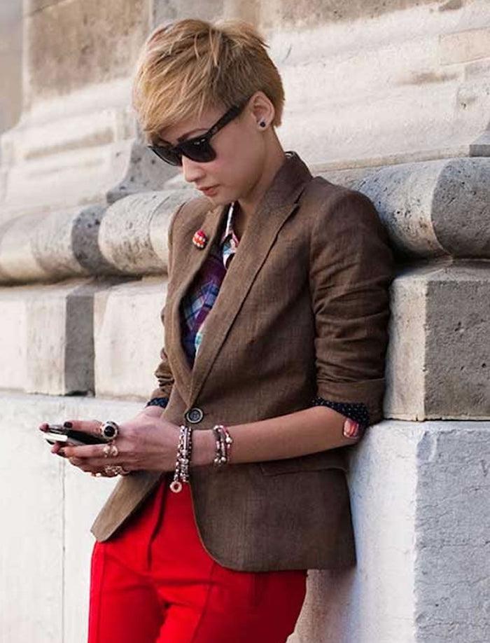 cupe courte effilée avec frange blonde femme au pantalon rouge veste marron chemisier violet et lunettes de soleil noires