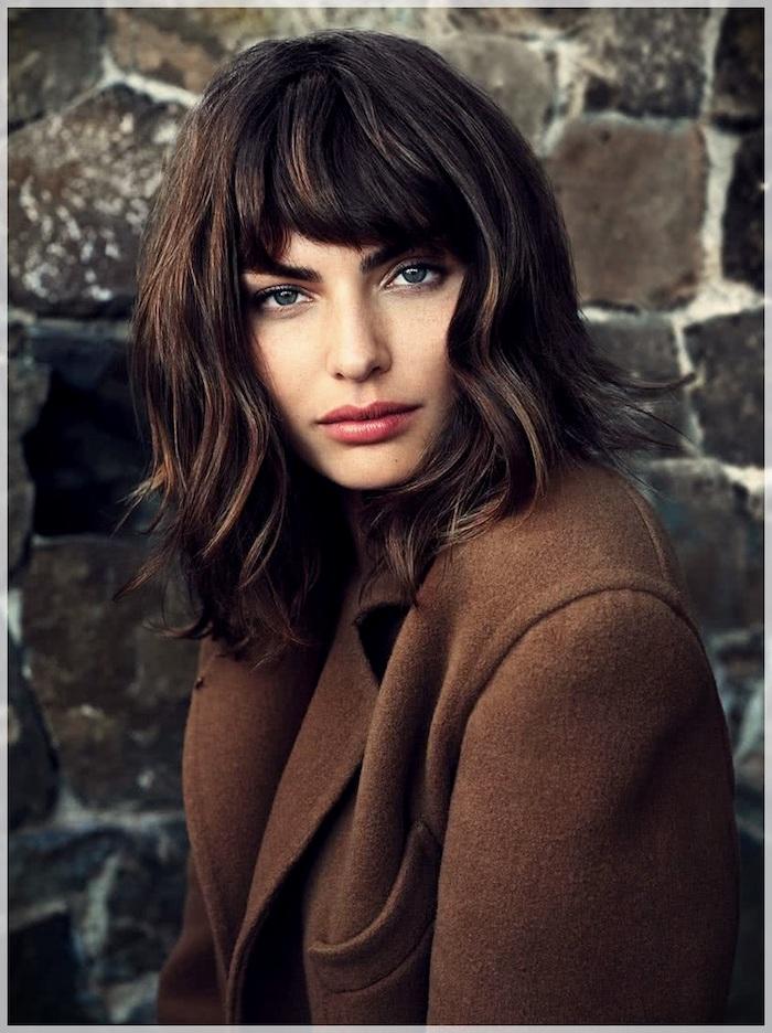 décoiffée coupe courte femme 2021 tendance brune au manteau marron devant un mur de tuiles