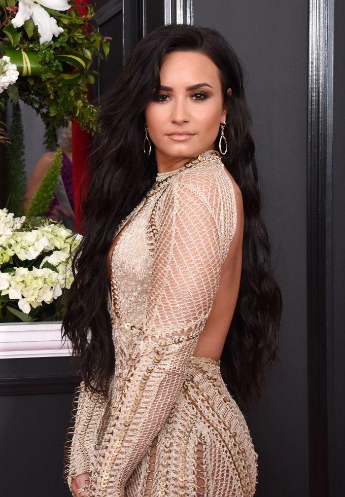 demi lovato avec coloration cheveux noirs coupe cheveux longs 2021 ondulés avec mèches sur le coté robe tricot