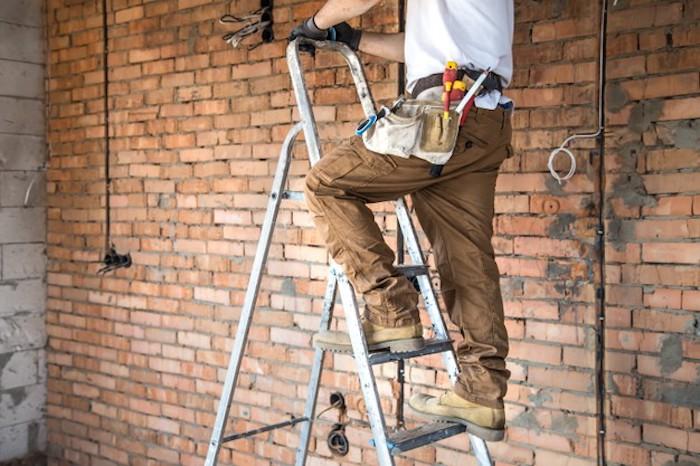 electricien pantalon beige pour homme avec оutiles mur en brique