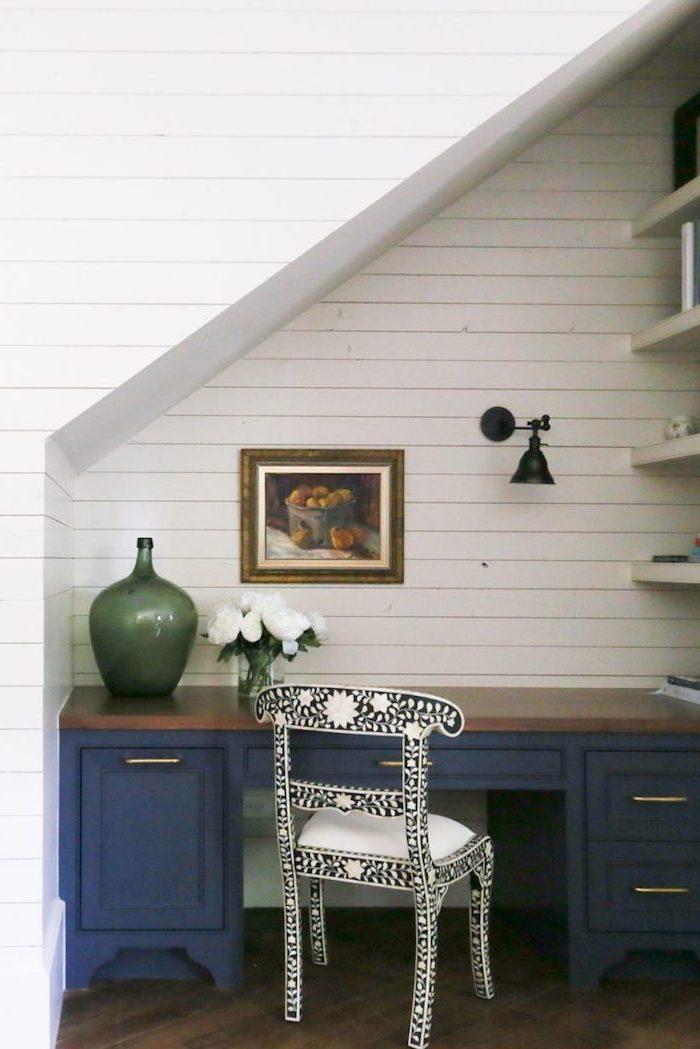 espace perdu cage d escalier étagères blanches mur de planches de bois blanc contraste avec le bureau bleu vase vert cadre de photo sur le mur chaise en noir et blanc