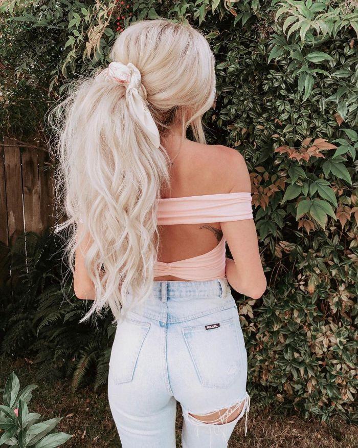 exempe de cheveux dense coupés en dégradé blond noués en queue de cheval grosse avec des mèches libres