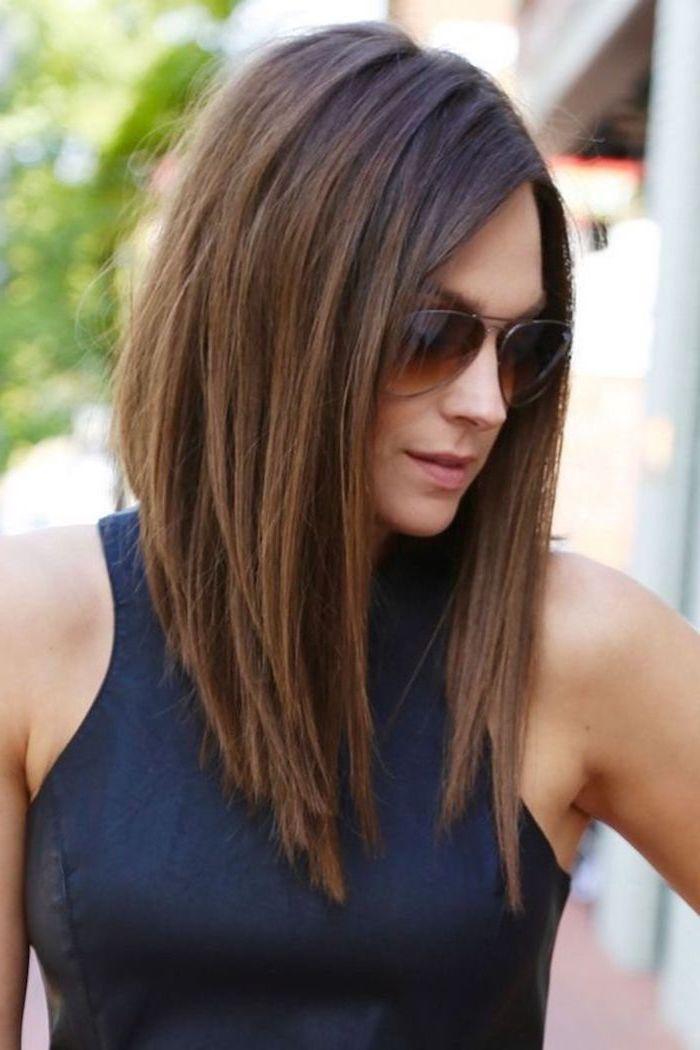 femme au carré asymétrique chatain lunettes de soleil marron au top bleu foncé