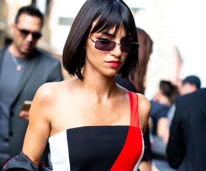 femme au carré court lisse avec frange droite fine lunettes de soleil noires en robe en noir blanc et rouge