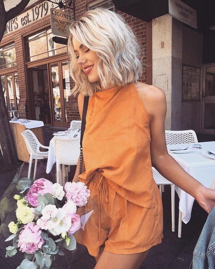 femme souriante bouquet de fleurs tenue orange foncé au carré mi long wavy blond
