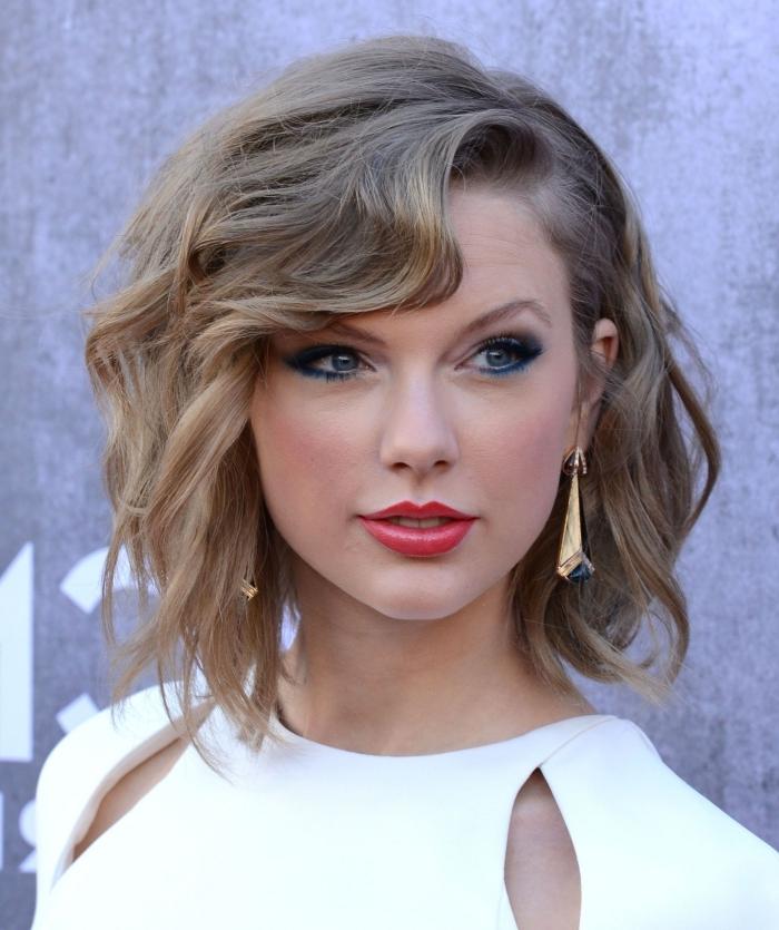 frange bouclée coiffure célébrité de soirée maquillage rouge lèvres eye liner bleu boucles d oreilles