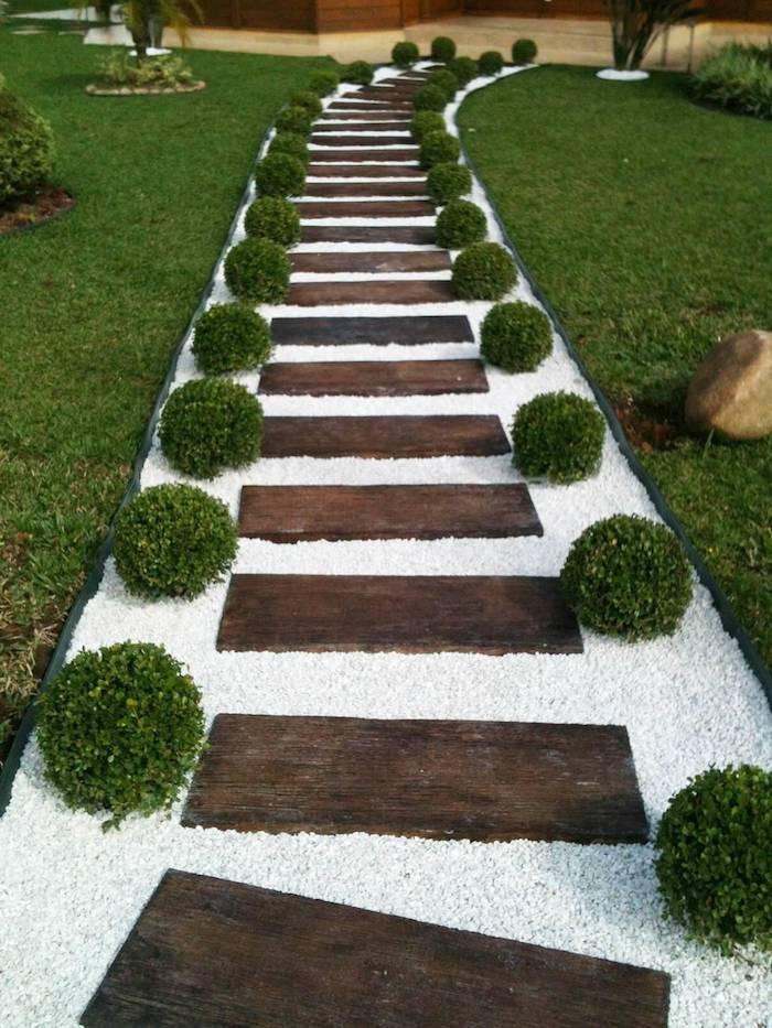 idée déco jardin avec gravier en blanc allée en bois et bordures en petits buissons