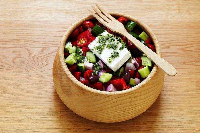 idée salade composée bol en bois plein de légumes fourchette en bois table de bois