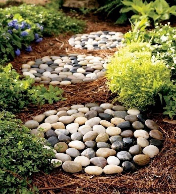 idee deco jarddin avec cailloux beiges et gris en forme de nids et des plantes vertes
