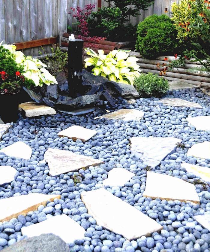 idee deco jardin avec cailloux bleus et pierres fontaine et fleurs dans le jardin