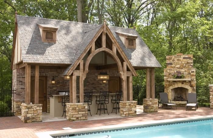 jardin avec piscine couverte revetement façade briques pierres chaises de bar extérieure fer forgé