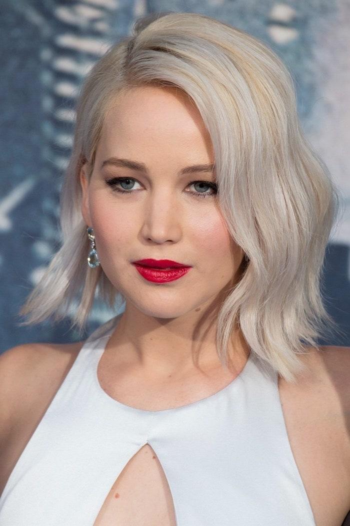 jennifer lawrence au carré dégradé et wavy coloration blond polaire rouge à lèvres rouge en robe blanche