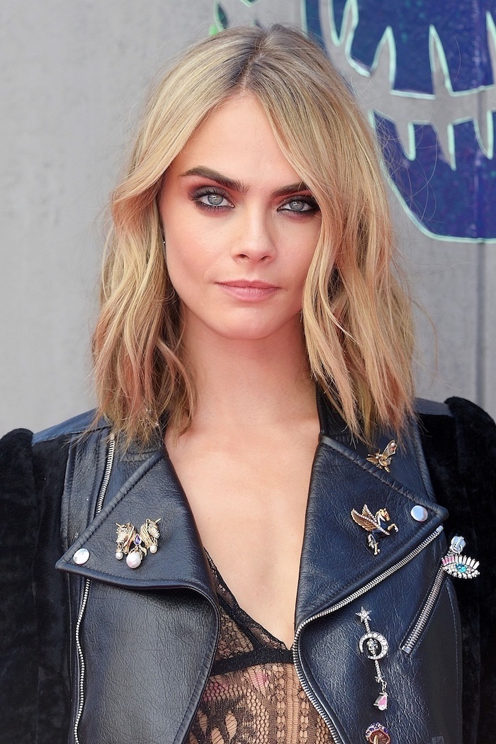 kara delevin à la coupe carré dégradé mi long blond avec mèches roses yeux les bleux soulignés en veste en cuir noir et top noir en dentelle