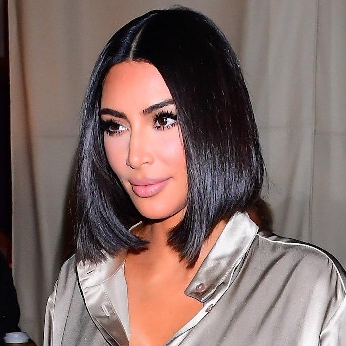 kim kardashian au carré asymétrique noir lisse avec raie au milieu en chemisier argenté