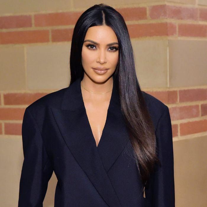 kim kardashian aux cheveux tres long et lisses chatain foncé avec raie au milieu de la tete