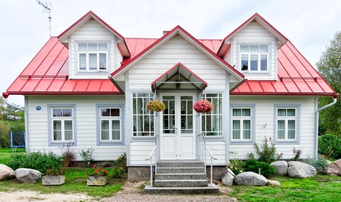 maison extérieure façade panneaux blancs isolation thérmique toit rouge fenêtre jardin aménagement paysager