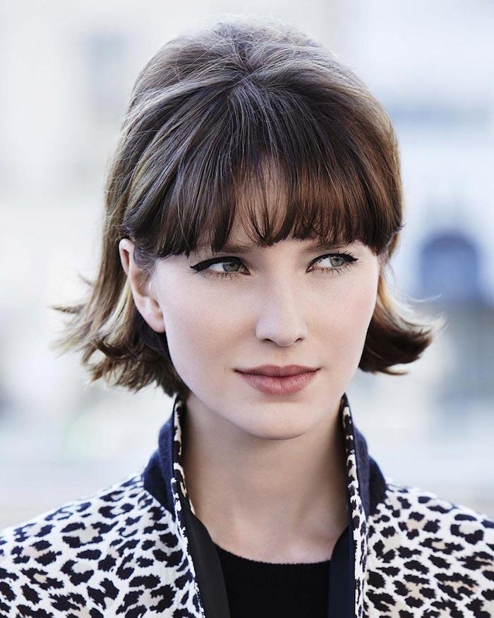 moderne coupe cheveux court avec frange droite effilée femme au maquillage discret à la veste en blanc et noir