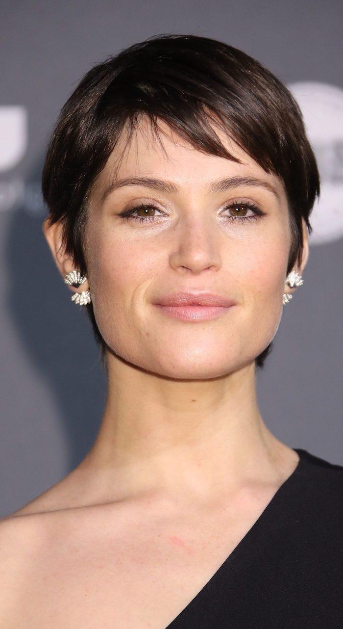 moderne coupe courte femme avec frange brune femme aux boucles d oreilles élégantes et à la tenue de soirée