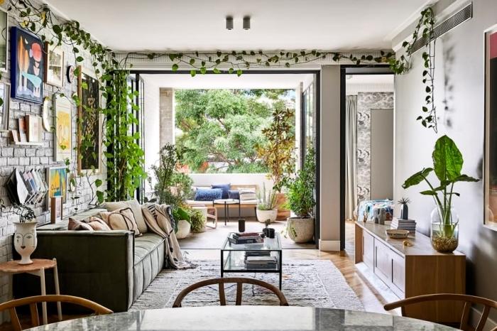 mur briques canapé velours vert plante retombante intérieur cache pot visage table verre salon