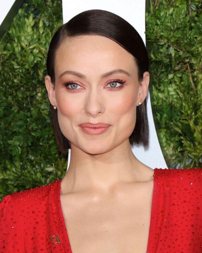 olivia wilde carré lisse court au style élégant maquillage discret boucles d'oreilles à la robe rouge