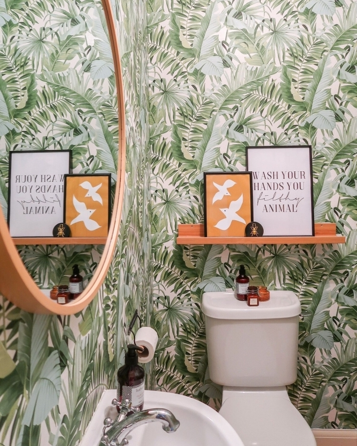 papier peint toilette motifs jungles feuilles vertes étagère bois peinture orange cadres décoratifs