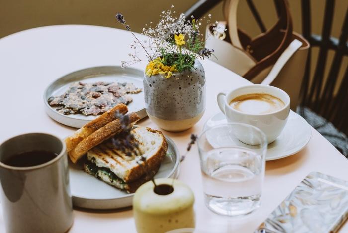 petit déjeuner table bouquet de fleurs vase gris mug thé couleur terre assiette ronde vaisselle tendance
