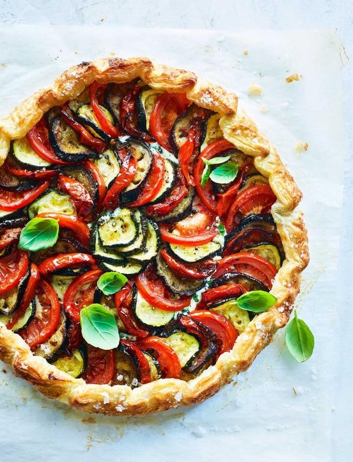 quiche salée forme ronde pâte brisée tomates rondelles courgettes feuilles de basilic poivrons rouges