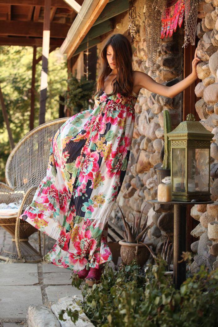 robe champetre chic à fleurs multicolores femme aux cheveux marron lâchés devant la maison