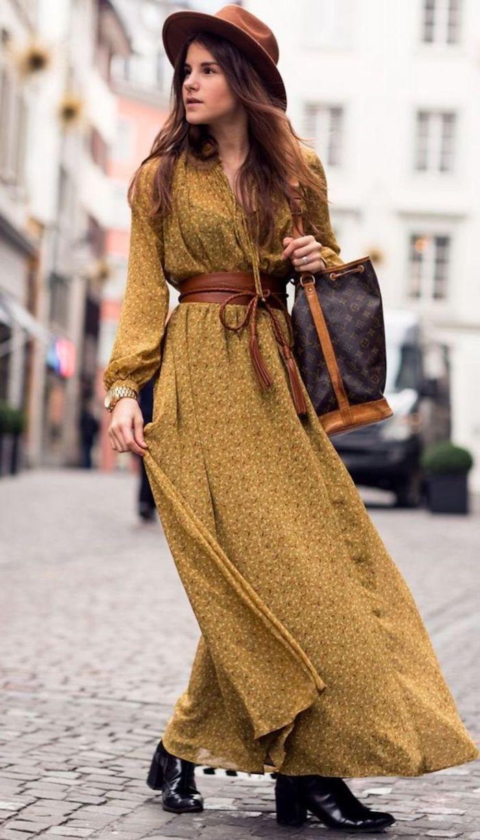 robe longue fleurie bohème ceinturée chapeau à bord bottines noires montre dorée et sac à main en noir et camel