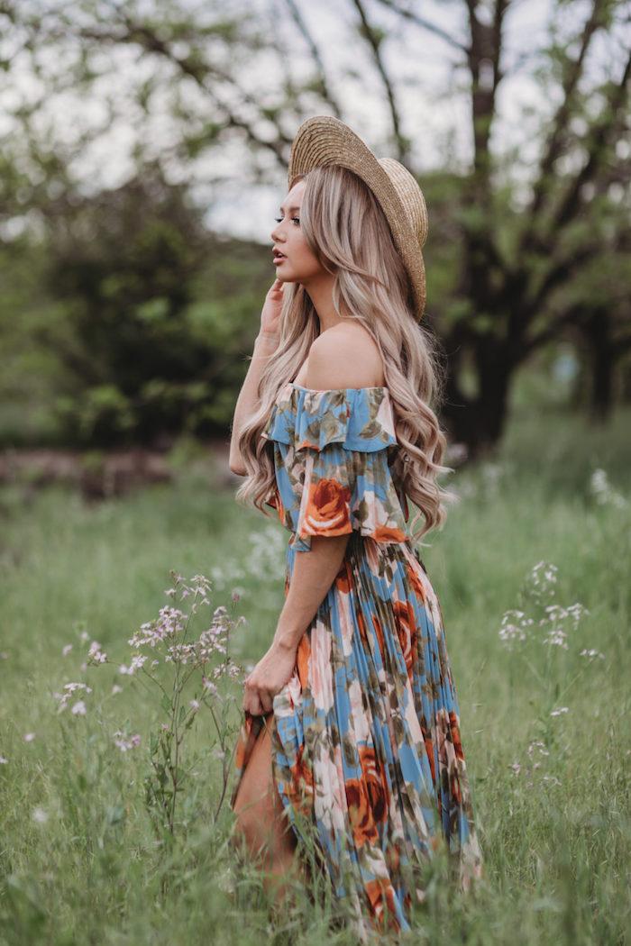 robe longue fleurie bohème femme au cheveux blonds à la capeline dans des champs