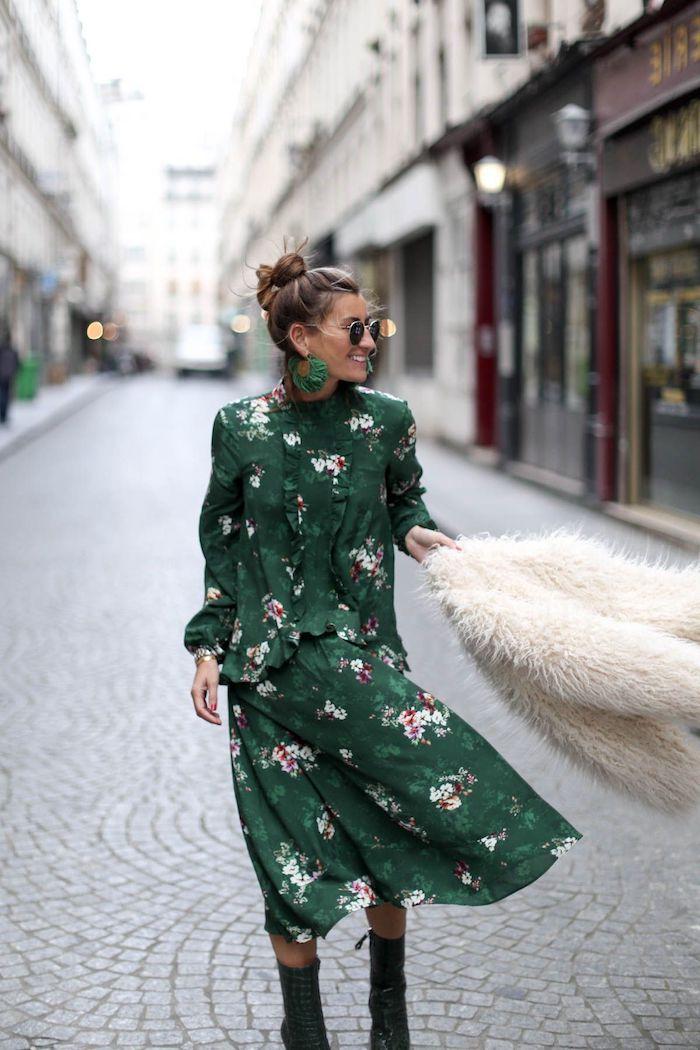 robe longue fleurie bohème fond vert foncé avec veste en fourrure bottines et lunettes de soleil noires coiffure en chignon