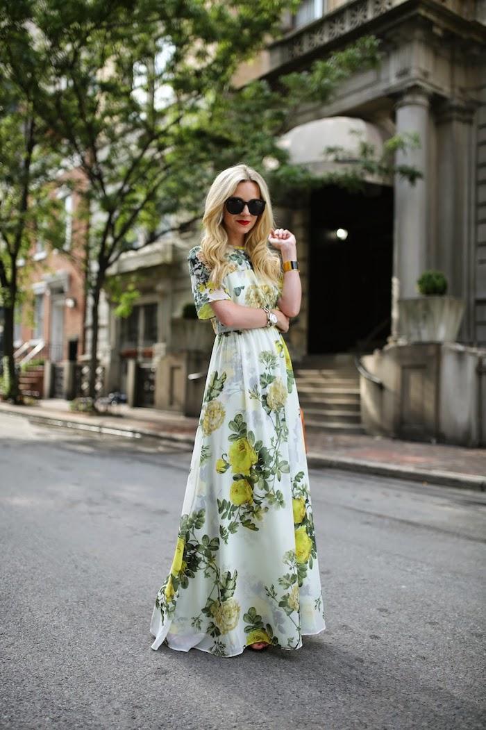 robe longue fleurie fond blanc femme aux lunettes de soleil noires et cheveux blonds ondulés