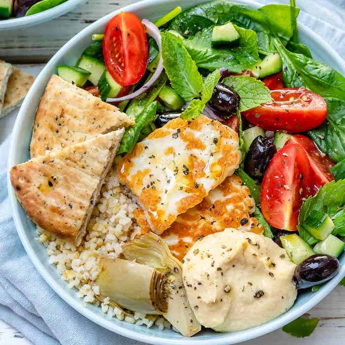 salade de tomates orifinale avec du pain plat houmous épinard du blé olives et de la menthe