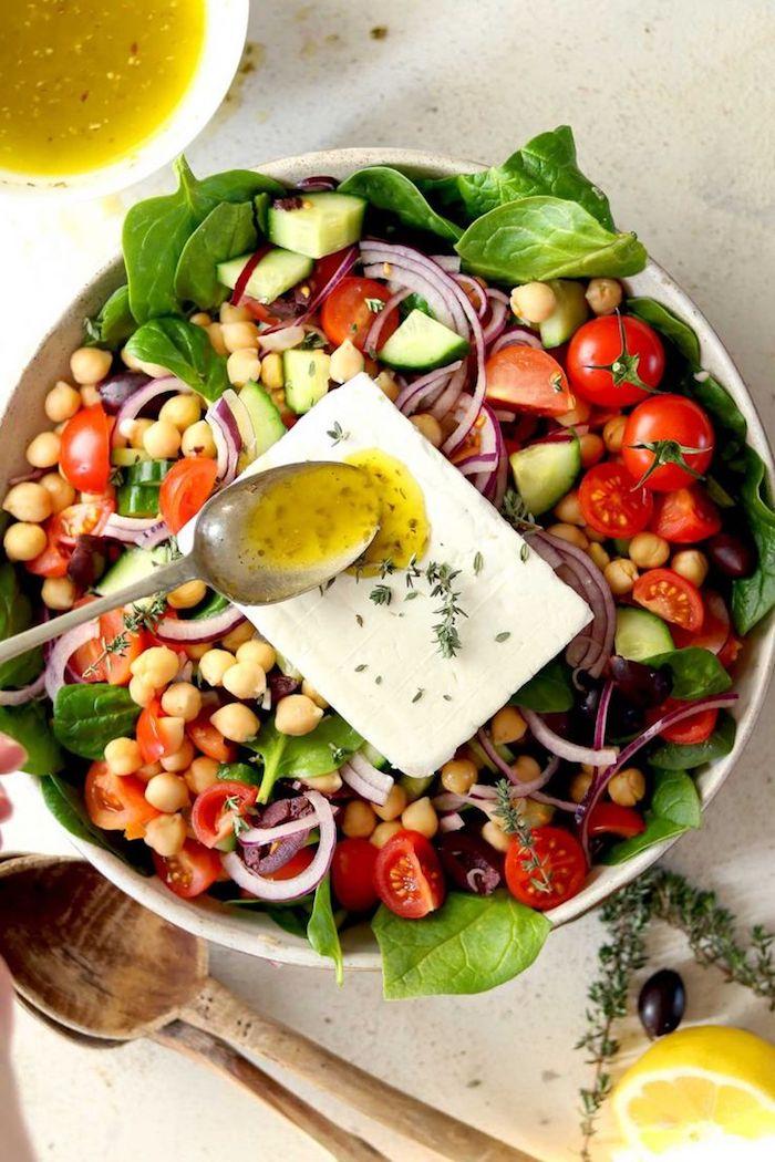 salade grecque saladier plein de concombres tomates olives épinards oignons feta et pois chiche
