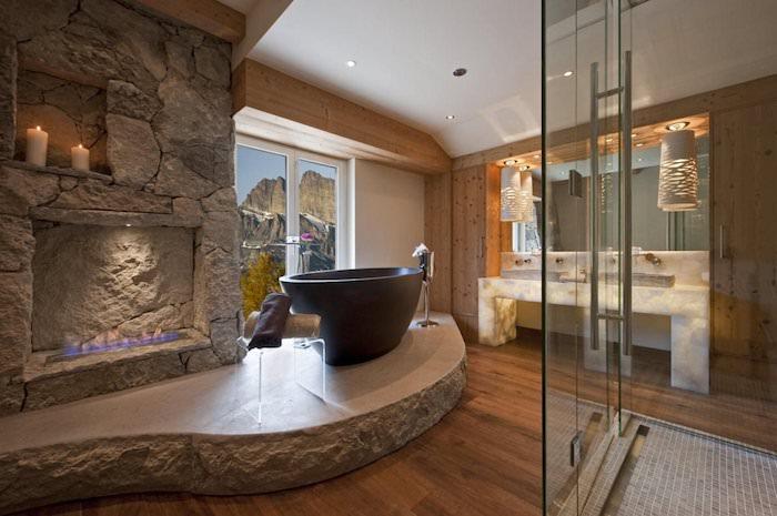 salle de bain de luxe avec cheminée et bougies baignoire en pierre plancher en bois