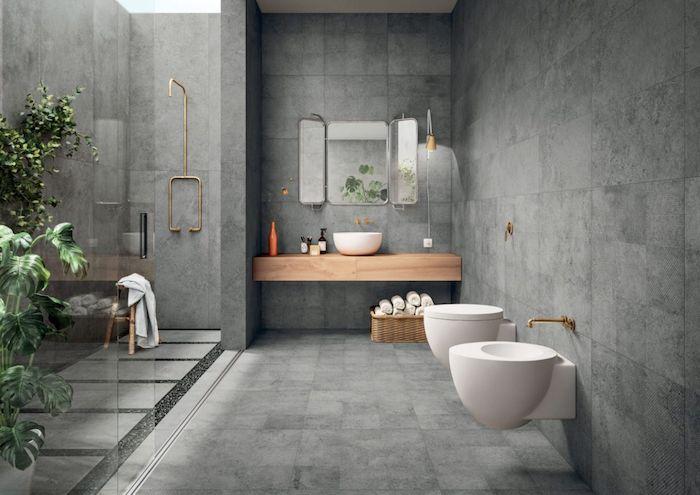 salle de bain pierre naturelle et bois murs et plancher en gris foncé accents en laiton plantes dans la salle de bain