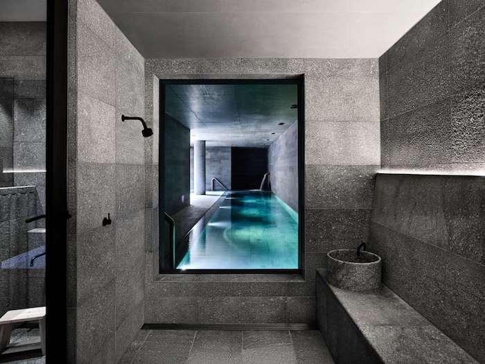 salle de bain travertiin et ardoise accents en noir piscine d'intérieur