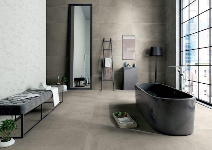 salle de bain travertin et noir très stylé échelle lampe cadre de miroir et baignoire en noir